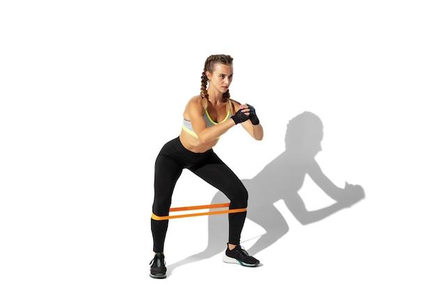Asseyez-vous. belle jeune athlète féminine pratiquant sur un mur blanc, portrait avec des ombres. modèle de coupe sportive en mouvement et en action. musculation, mode de vie sain, concept de style.