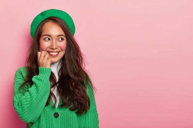 Assez belle fille asiatique avec une expression heureuse, porte un béret vert à la mode et un pull en tricot, touche le menton, imagine un moment agréable à l'esprit