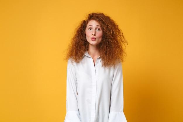 Assez drôle de jeune femme rousse en chemise blanche décontractée posant isolée sur un mur orange jaune