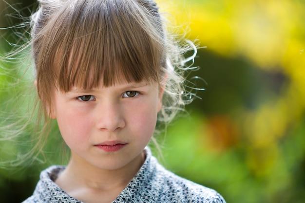 Assez drôle de mauvaise humeur jeune enfant fille en plein air se sentir en colère et insatisfait sur le concept de colère des enfants vert été floue.