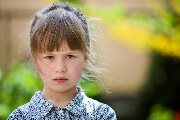Assez drôle de mauvaise humeur jeune enfant fille en plein air se sentir en colère et insatisfait sur le vert d'été flou. les enfants s'énervent.