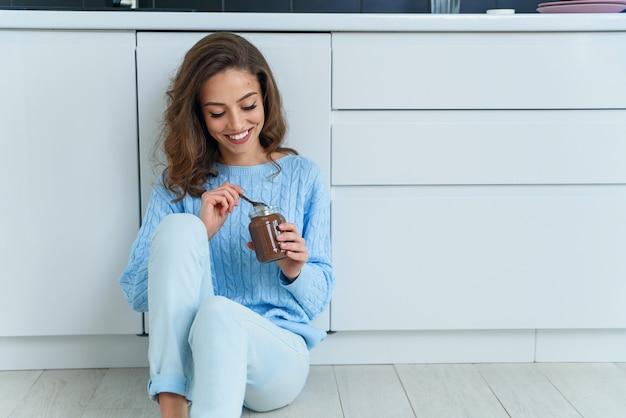 Assez exubérante jeune femme dans des vêtements élégants modernes bénéficiant d'un délicieux chocolat avec un joli sourire à l'intérieur de la cuisine