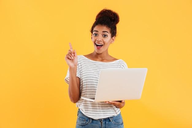 Assez gaie dame africaine et tenant un ordinateur portable isolé