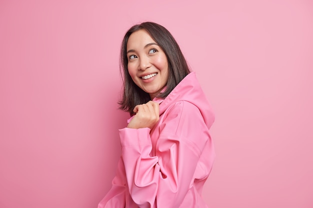 Assez heureuse, une femme asiatique brune se tient à moitié tournée contre le mur rose a la bonne humeur porte une veste élégante avec une capuche pense à quelque chose d'agréable pose heureuse à l'intérieur. notion d'émotions