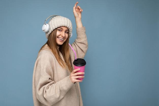 Assez heureuse jeune femme blonde souriante portant un pull d'hiver beige et un chapeau isolé sur bleu