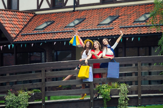 Assez heureux femmes lumineuses femmes filles vêtues de robes colorées et de hauts talons avec des sacs à provisions marchant dans la rue après le shopping