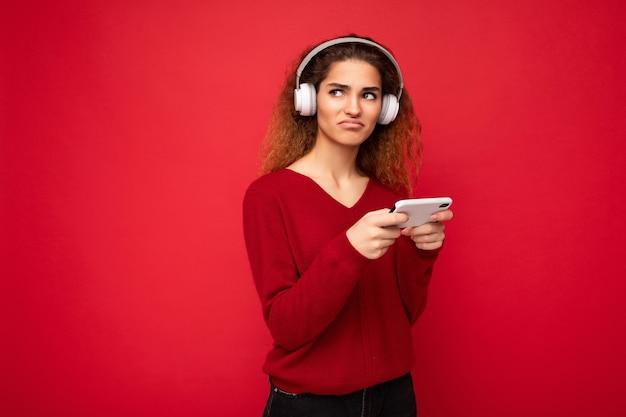 Assez insatisfaite triste jeune femme brune bouclée portant un pull rouge foncé isolé sur fond rouge