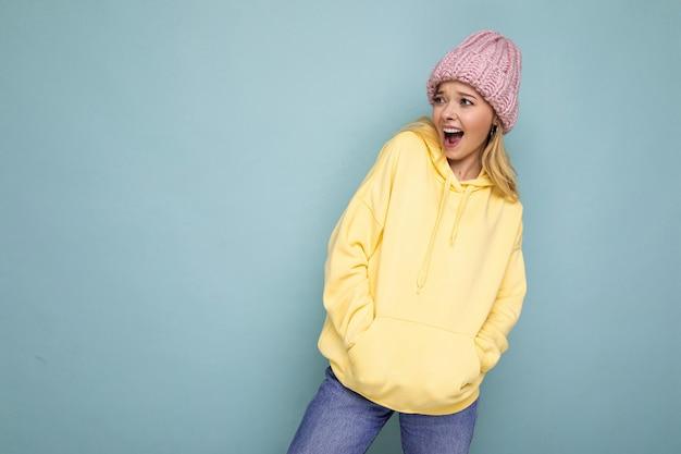 Assez positive heureuse jeune femme blonde isolée sur un mur de fond coloré portant des vêtements décontractés