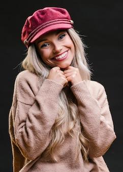 Assez souriante jeune femme debout près de fond noir en regardant la caméra
