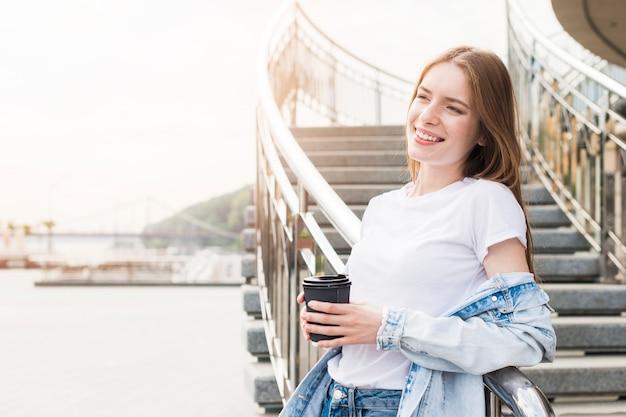 Assez souriante jeune femme se penchant sur la rambarde métallique