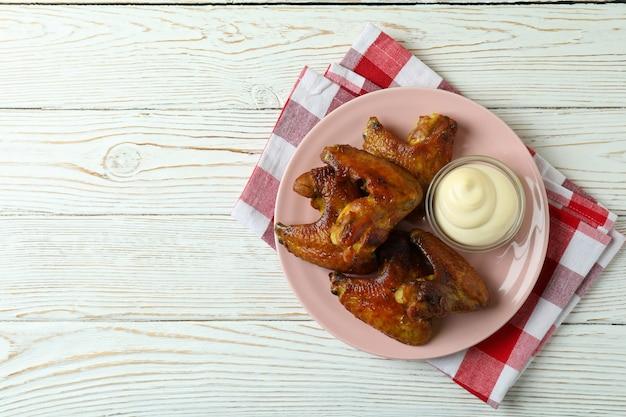 Assiette avec ailes de poulet au four et sauce sur torchon sur fond de bois