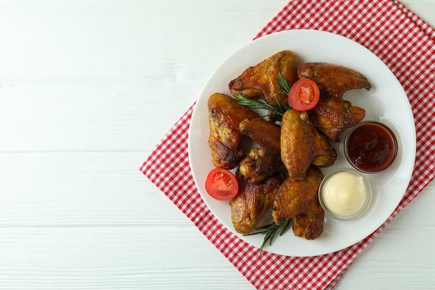 Assiette avec ailes de poulet au four et sauces sur fond de bois