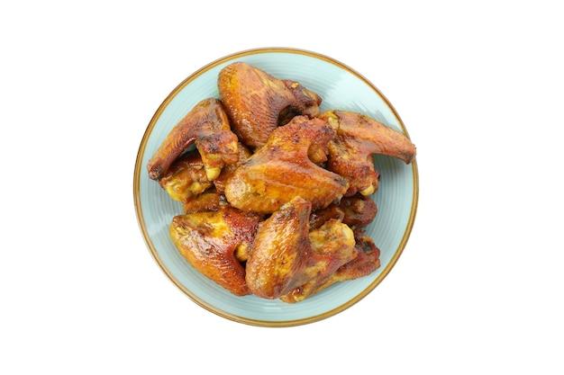 Assiette avec des ailes de poulet cuit au four isolé sur fond blanc