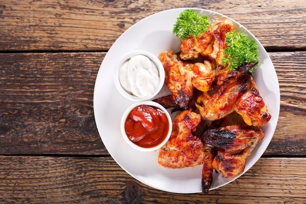 Assiette d'ailes de poulet frit sur table en bois, vue du dessus