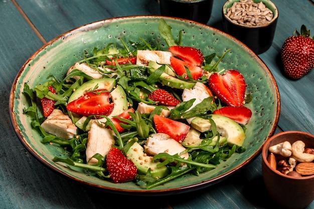 Assiette avec un aliment diététique céto. salade de fraises avec roquette, poulet, avocat et fraises. fond de recette de nourriture. fermer