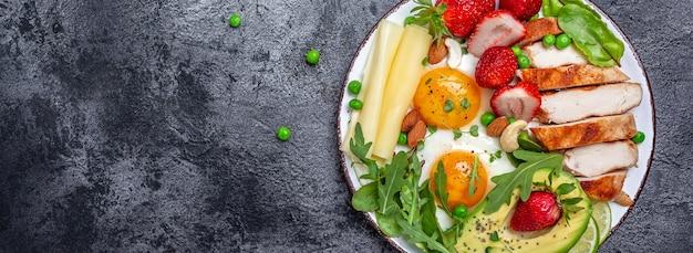 Assiette avec un aliment de régime céto. egguf frit, avocat, fraise, filet de poulet grillé, fromage, noix et roquette. petit-déjeuner céto. régime cétogène. concept d'alimentation saine, vue de dessus.