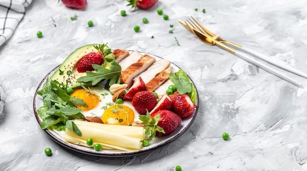 Assiette avec des aliments diététiques céto. petit-déjeuner keto uf au plat, avocat, fraise, filet de poulet grillé, fromage, noix et roquette, régime cétogène. concept d'alimentation saine, vue de dessus,