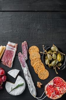 Assiette d'antipasti avec du fromage frais, du pain et des olives, sur une table en bois noir, mise à plat avec espace de copie pour le texte