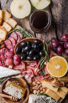 Assiette antipasti italienne traditionnelle. fromages assortis sur planche à découper en bois. fromage brie, tranches de cheddar, gogonzola, raisins de noix, olives, prosciutto, romarin et verre de vin rouge. vue de dessus