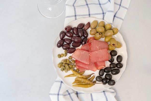 Assiette d'antipasto avec des câpres et des olives de cornichons au salami basturma sur fond neutre vue de dessus avec ...