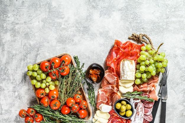 Assiette d'antipasto charcuterie aux raisins, prosciutto, tranches de jambon, bœuf séché, salami chorizo, fuet, camembert et fromage de chèvre