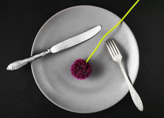 Assiette avec des appareils et une fleur d'ail sauvage
