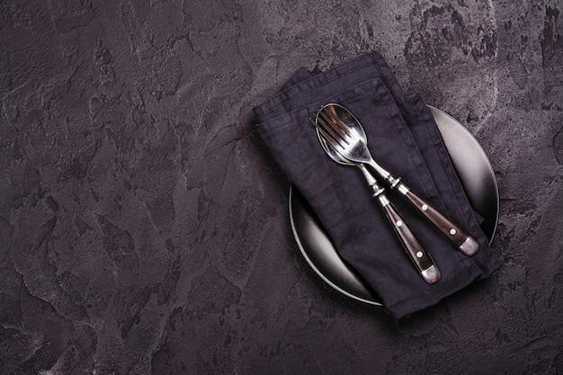 Assiette et argenterie vides sur fond de pierre sombre. vue de dessus