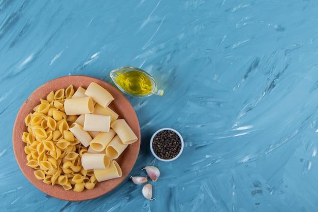 Une assiette en argile de pâtes non cuites avec de l'huile et des tomates rouges fraîches sur fond bleu.