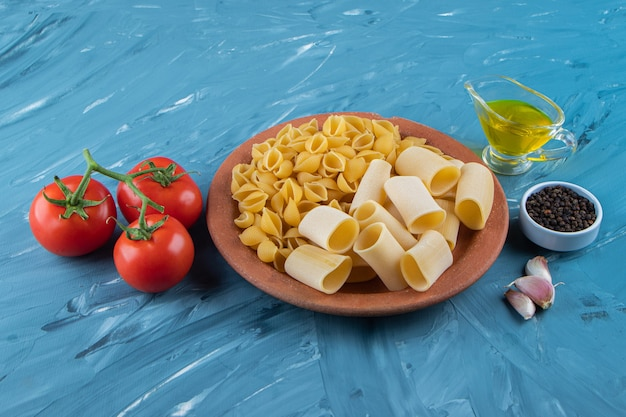 Une assiette d'argile de pâtes non cuites avec de l'huile et des tomates rouges fraîches sur une surface bleue .