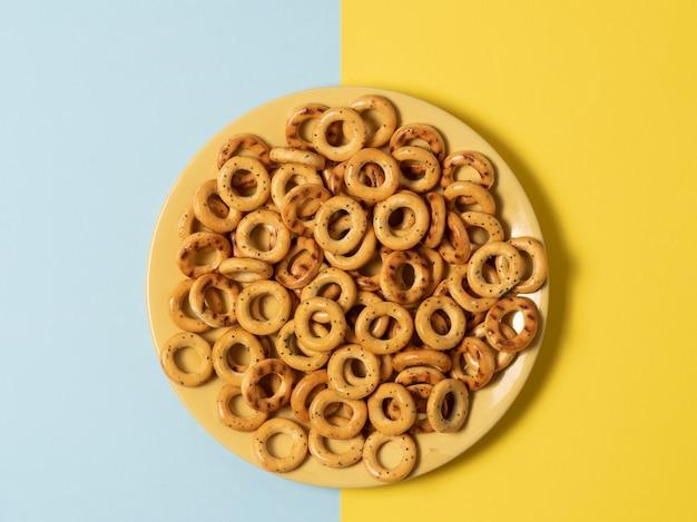 Assiette avec des bagels de pain se dresse sur des arrière-plans multicolores bleu et jaune
