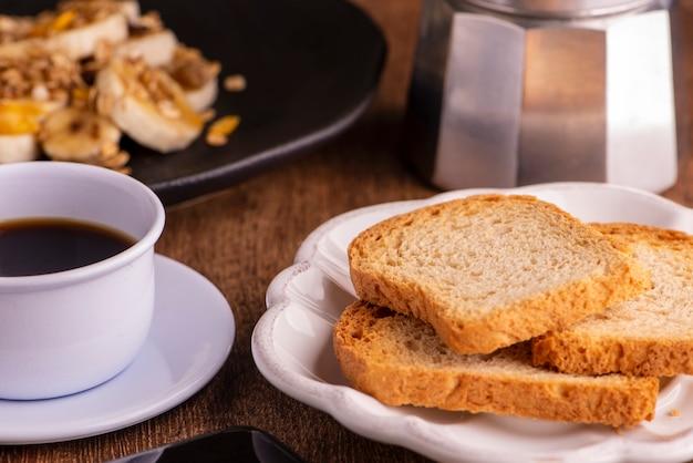 Assiette avec banane en tranches, granola, fruits confits et miel, pain grillé et une tasse de café