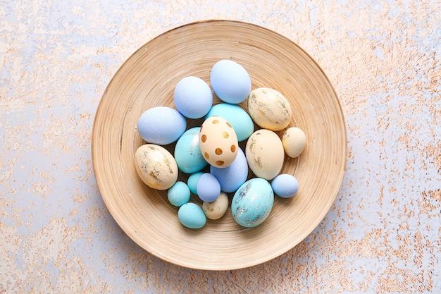Assiette avec de beaux œufs de pâques à la lumière