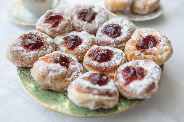 Une assiette de beignets remplis de confiture et enrobés de sucre.