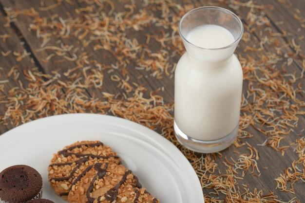 Assiette de biscuits à l'avoine avec petits gâteaux et un pichet en verre de lait
