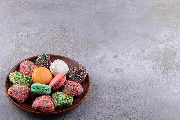 Assiette de biscuits colorés et macarons avec des pépites sur la table.