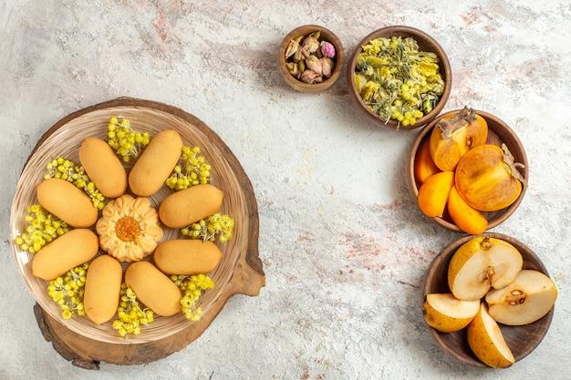 Une assiette de biscuits et différentes fleurs et fruits secs sur sol en marbre