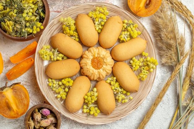 Une assiette de biscuits et de fleurs séchées et d'emmers et de palmiers sur marbre