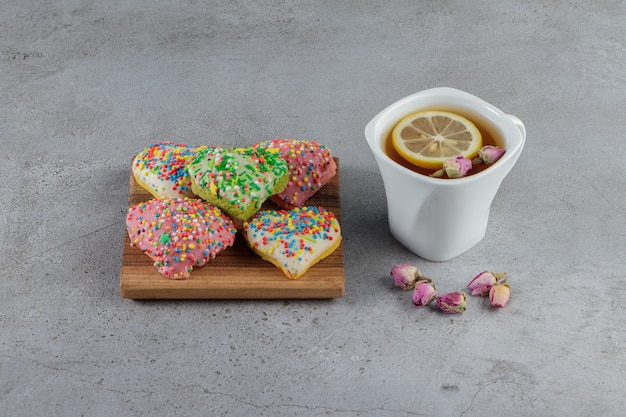 Une assiette de biscuits en forme de coeur avec des pépites et une tasse de thé chaud