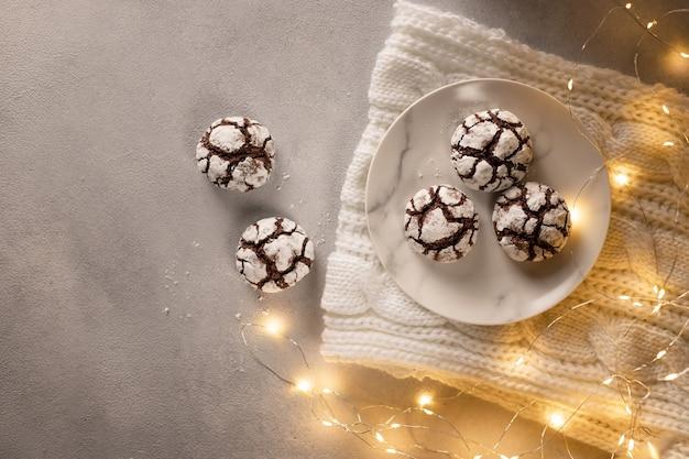 Assiette avec des biscuits froissés au chocolat faits maison sur une ambiance de noël à carreaux confortable