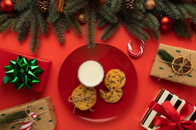 Assiette avec biscuits et lait sur fond rouge