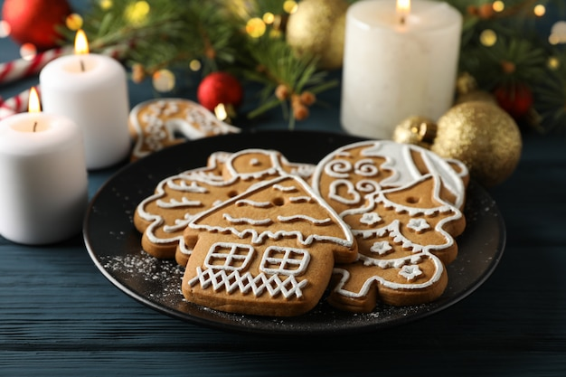 Assiette avec des biscuits de noël, arbre de noël et jouets sur bleu, espace pour le texte. fermer