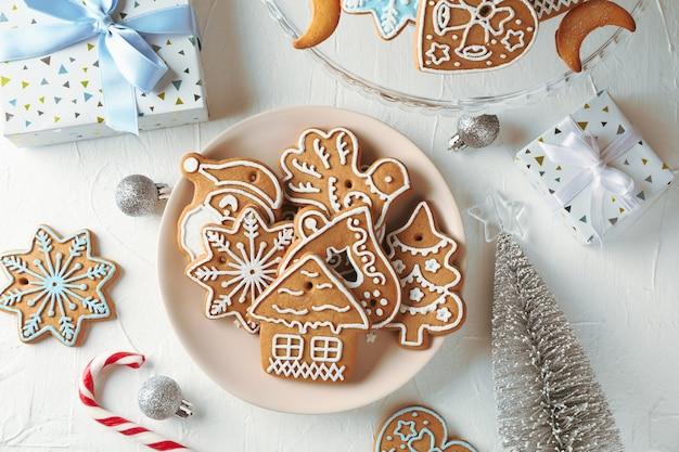Assiette avec des biscuits de noël, des arbres de noël, des jouets, des coffrets cadeaux sur blanc, vue du dessus