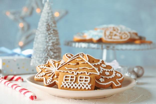 Assiette avec des biscuits de noël, des arbres de noël, des jouets, des coffrets cadeaux sur tableau blanc, sur bleu, gros plan