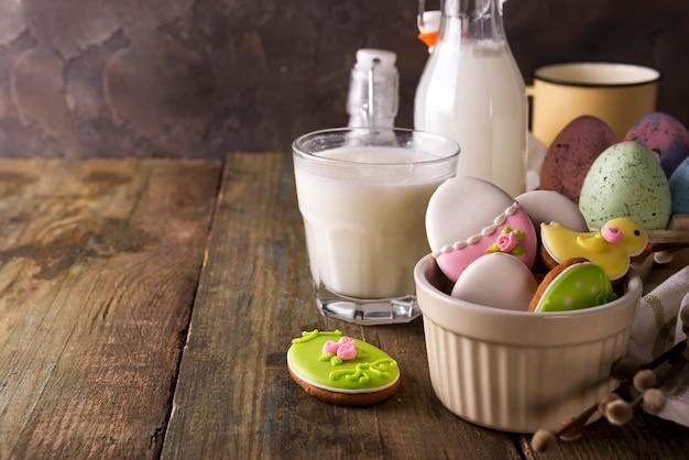 Assiette avec des biscuits de pâques colorés et un verre de lait, style rustique