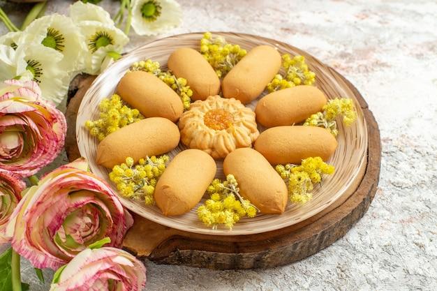 Une assiette de biscuits sucrés sur un plateau en bois et de belles fleurs de couleur sur sol en marbre blanc