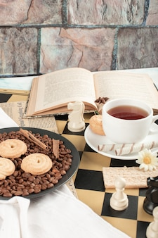 Assiette de biscuits et une tasse de thé sur l'échiquier