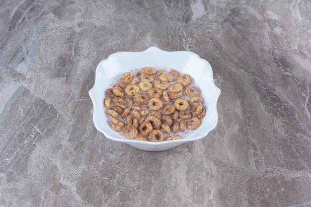 Une assiette blanche d'anneaux de céréales au chocolat avec du lait sur une table grise.