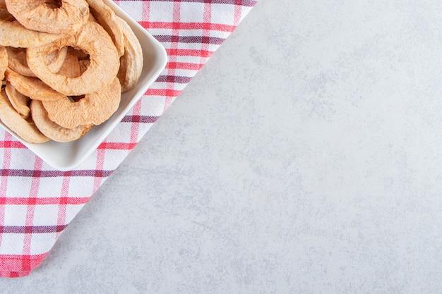 Assiette blanche d'anneaux de pommes séchées saines sur fond de pierre.