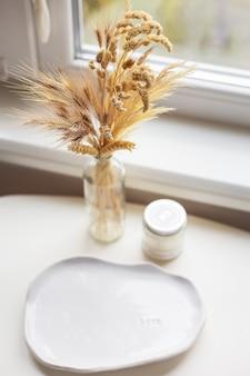 Une assiette blanche en argile artisanale, une bougie, un vase se dresse près de la fenêtre