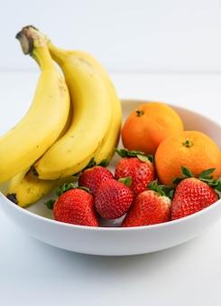 Assiette blanche avec bananes oranges et fraises